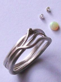 sinuous ring design next to an opal and two diamonds